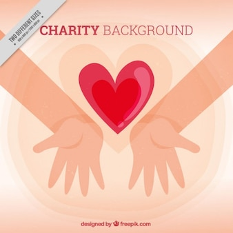 Hands with a red heart charity background