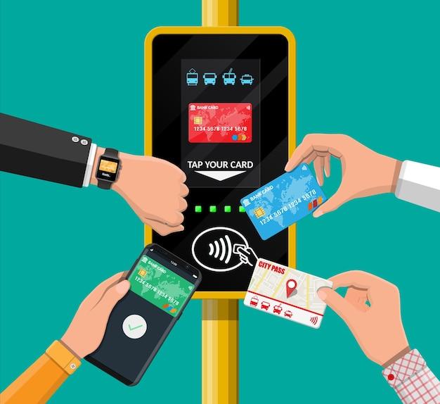 Руки с транспортной картой, смартфоном, умными часами и банковской картой возле терминала.
