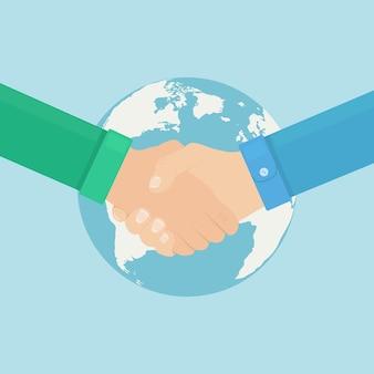 Рукопожатие на фоне земного шара. руки разных людей