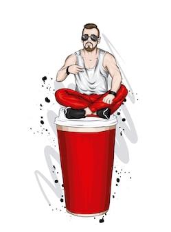 Красивый парень в стильной одежде сидит на стакане кофе