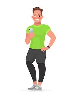 잘 생긴 남자는 그의 손에 스마트 폰을 들고있다. 스포츠 피트니스 응용 프로그램입니다.