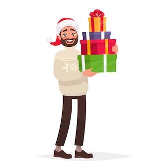 Красивый мужчина, одетый в свитер и рождественскую шляпу, держит подарки