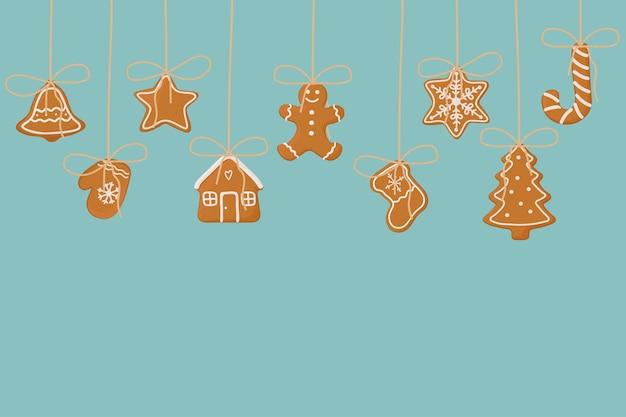 青い背景にジンジャーブレッドクッキーをぶら下げバナーグリーティングカードのクリスマステンプレート