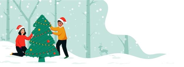 幸せの男の子と女の子が降雪の森で一緒にクリスマスツリーを飾った