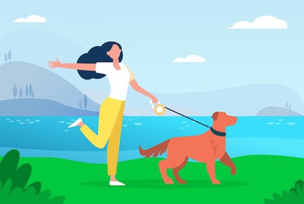 Счастливая активная женщина гуляет с собакой на поводке на открытом воздухе.
