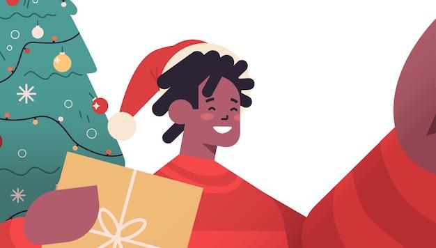 カメラを持って、モミの木の近くで自分撮りを撮ってサンタ帽子をかぶった幸せなアフリカ系アメリカ人の男新年クリスマス休暇お祝いコンセプト横向きの肖像画ベクトル図