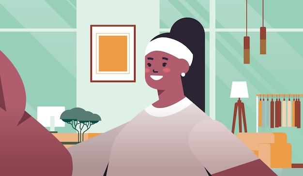 幸せなアフリカ系アメリカ人の女性がスマートフォンのカメラの女の子で自分撮りを撮ってセルフ写真のリビングルームのインテリアの横向きの肖像画のベクトル図