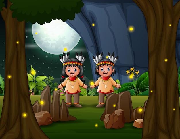 Счастливый американских индейцев мальчик и девочка в ночном пейзаже