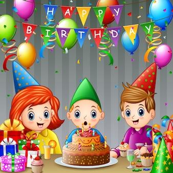 Счастливый мальчик дует свечи рождения с друзьями