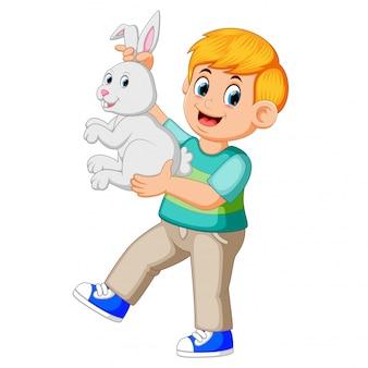 Happy boy holding a rabbit