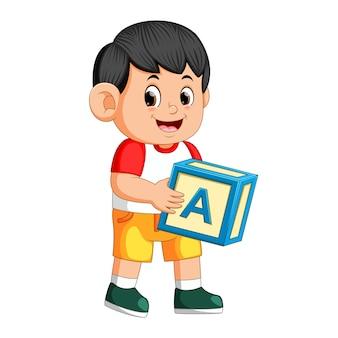 Счастливый мальчик держит кубик алфавита