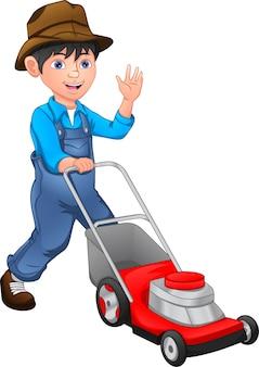 幸せな少年は芝刈り機で芝生を刈っています。