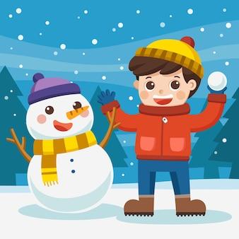 Счастливый мальчик играет на открытом воздухе в снегу. мальчик веселится со снеговиком на снежной зимней прогулке.