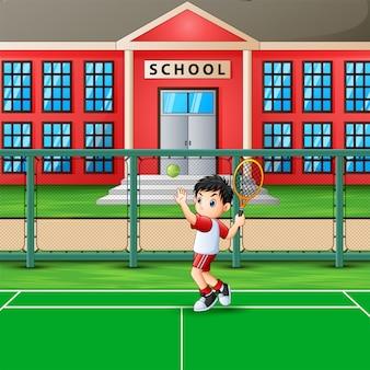 学校のコートでテニスをして幸せな少年