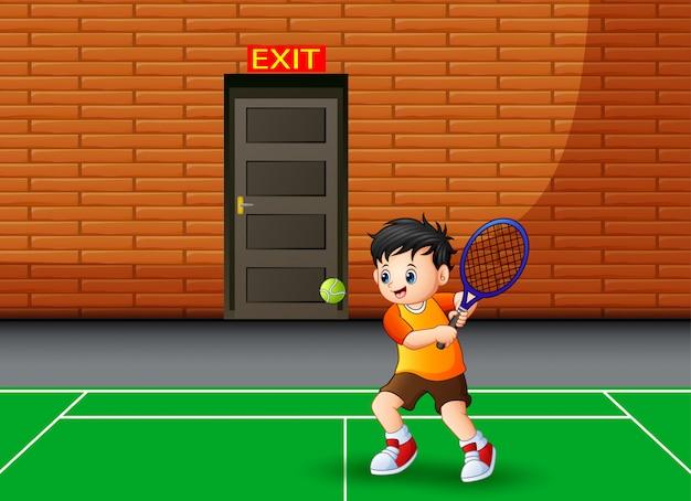 Happy boy playing tennis indoor