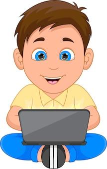 Счастливый мальчик играет с ноутбуком на белом фоне