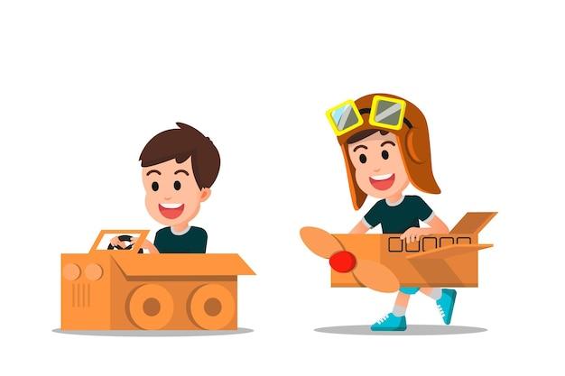 段ボールで作られた車や飛行機で遊ぶ幸せな少年