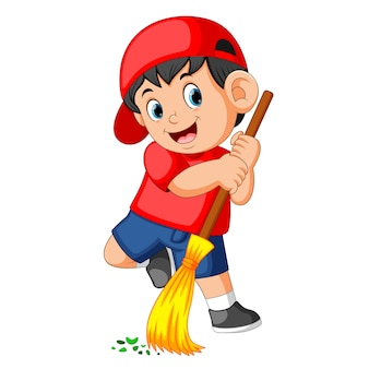 Happy boy using the red cap sweep the trash with the long broom