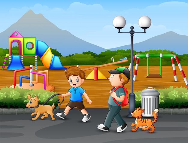 Happy boy walking wit pet in the park