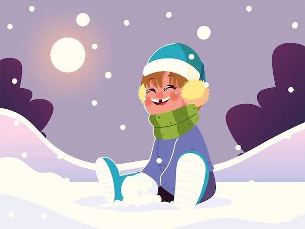 雪の中で座っている暖かい服を着た幸せな少年