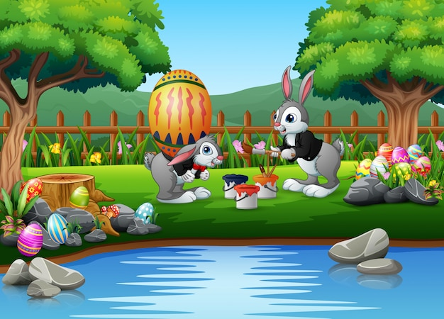 Happy bunnies painting a large easter egg