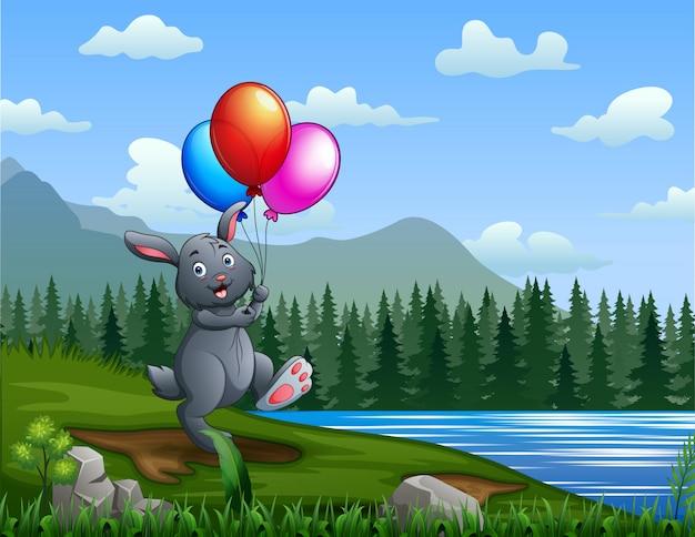 川でカラフルな風船を持って幸せなウサギ