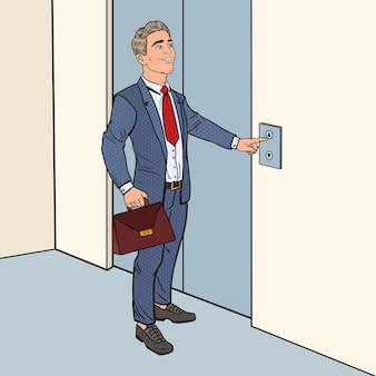 エレベーターボタンを押すブリーフケースを持つ幸せなビジネスマン
