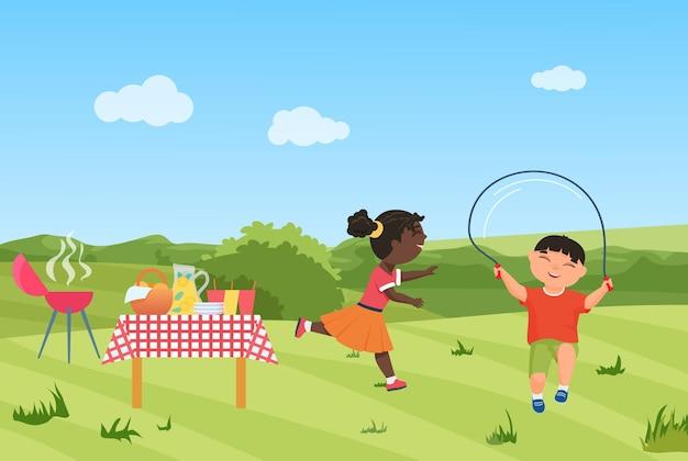 Счастливые дети веселятся на пикнике с барбекю вместе девочка бежит мальчик прыжки через скакалку
