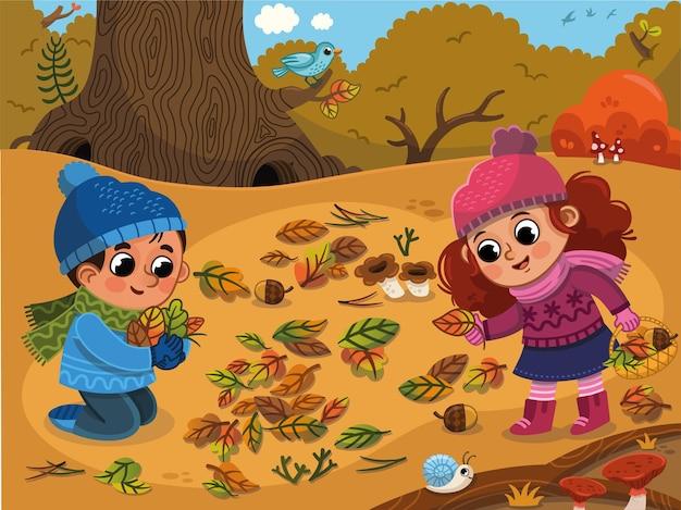 가을 공원에서 즐거운 시간을 보내는 행복한 아이들 겨울 옷을 입은 두 아이가 나뭇잎과 옥수수를 수집합니다