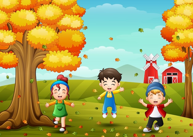 Happy children playing with autumn leaves