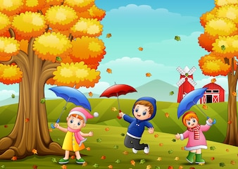 Happy children playing with umbrellas in farm landscape