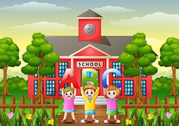 学校の建物の前にアルファベットを示す幸せな子供たち
