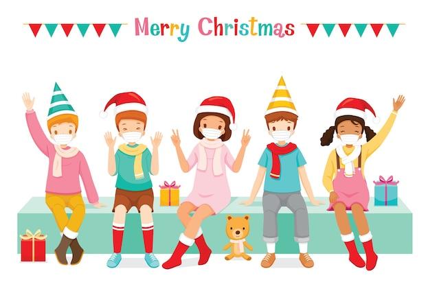 クリスマスの日に一緒に座っている幸せな子供たち