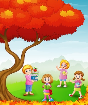 Happy children studying in the autumn trees