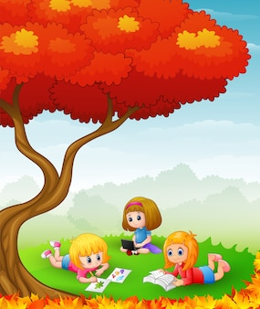 秋の木で勉強している子供たち
