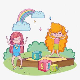 Happy childrens day, girls playing in sandbox with blocks park