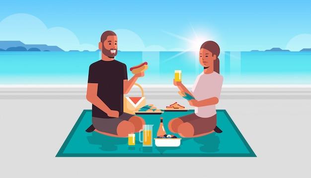 해변 피크닉 개념 바다 배경 평면 전체 길이 가로에서 함께 시간을 보내고 사랑에 주스 남자 여자를 마시는 핫도그를 먹고 담요에 앉아 행복 한 커플