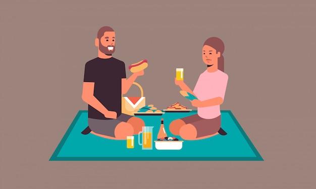 행복 한 부부 함께 피크닉 개념 평면 전체 길이 가로 데 시간을 보내고 사랑에 주스 남자 여자를 마시는 핫도그를 먹고 담요에 앉아