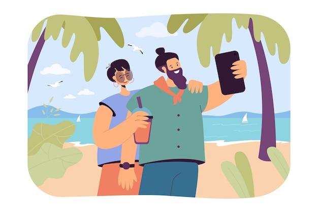 ビーチで電話で写真を撮る幸せなカップル