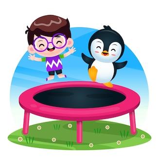 Счастливый милый мальчик и пингвин играют на батуте