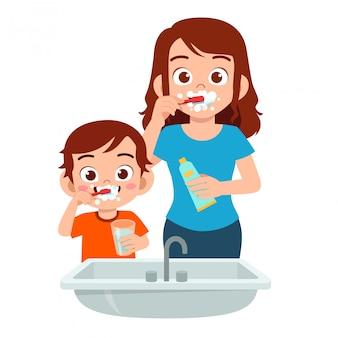 Happy cute kid boy brush teeth with mom