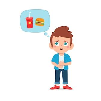 Счастливый милый ребенок мальчик чувствует голод, хочет поесть и думает о еде