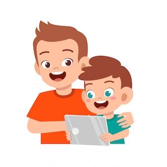 Happy cute kid boy leard internet with father