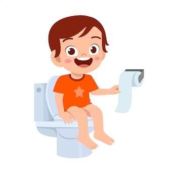 Happy cute kid boy sit on the toilet