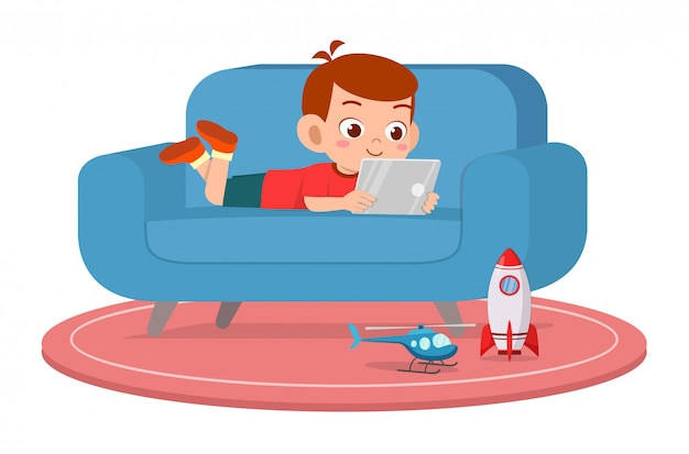 Happy cute kid boy use tablet on sofa
