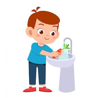 Happy cute kid boy wash vegetable fruit clean