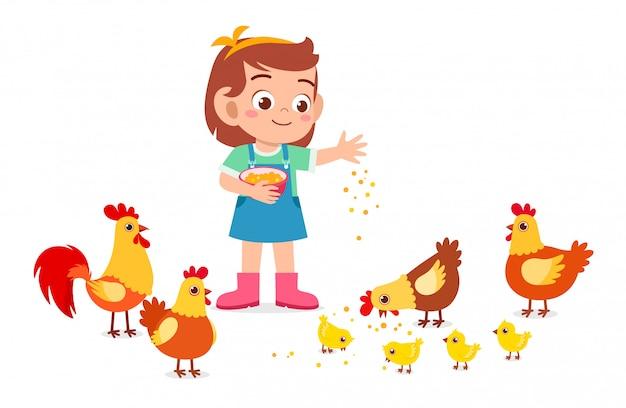 Happy cute kid girl feeding cute chicken