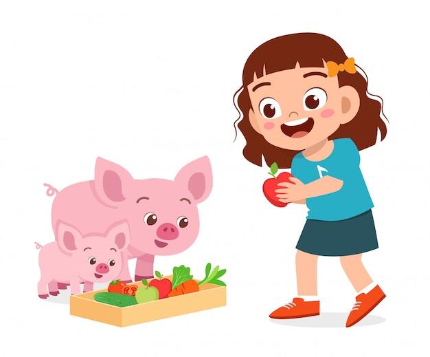 Happy cute kid girl feeding cute pig