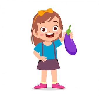 Happy cute kid girl holding fresh vegetable