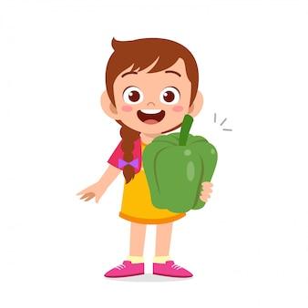 新鮮な野菜を持って幸せなかわいい子供女の子 Premiumベクター